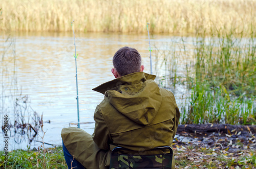 The fisherman sits on a stool a back