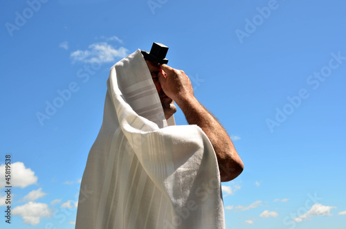 Jewish man pray to God under the open blue sky