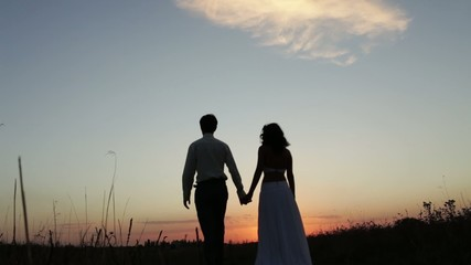 Bride and groom go into the sunset