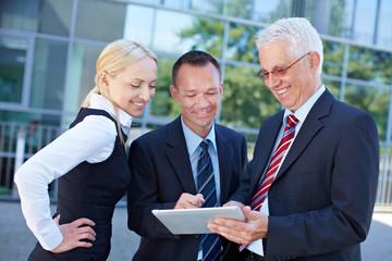 Business-Team schaut auf Tablet PC