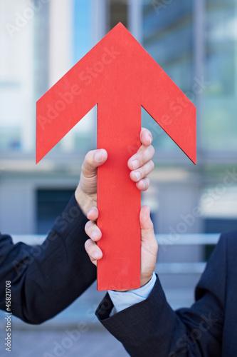Hände halten roten Pfeil