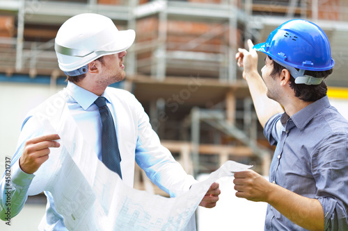 Engineer showing something to his partner at building site