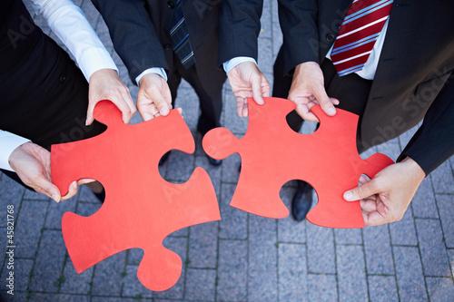 Hände halten Puzzlestücke