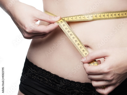 Young woman measures her waist circumference - isolated