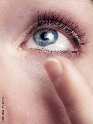 canvas print picture Young woman with blue eyes uses contact lenses - isolated