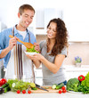Young Man Cooking. Happy Couple Eating Fresh Vegetable Salad