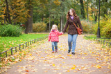 Mother and little daughter enjoying a beautiful autumn day outdo