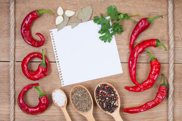 Red chili peppers, garlic, bay leaf, spices, paper on wood
