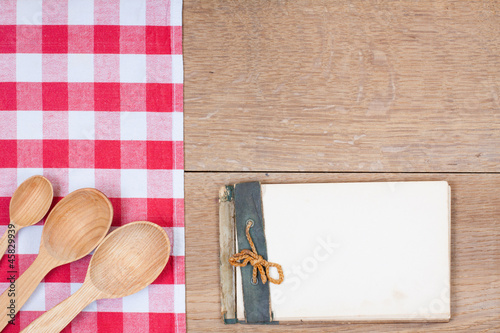 Red white tablecloth, spoons, old cookbook on wood background