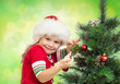 pretty preschool girl decorating Christmas tree