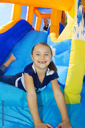 Kids playing on an inflatable slide bounce house