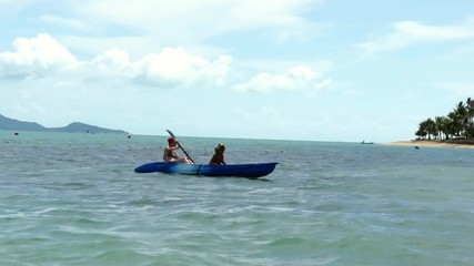 Mother and son kayaking at tropical sea