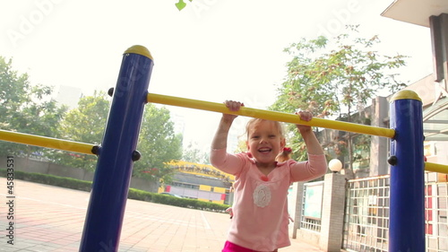 Happy little girl climbing in playground