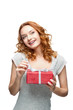 young red-haired happy smiling girl holding gift