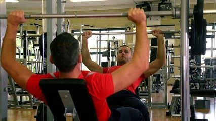 man at gym doing exercise with barbell