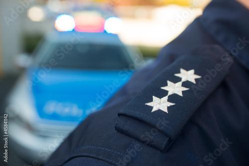 Leinwanddruck Bild Polizist vor Polizeiauto