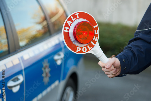 Polizist hält Polizeikelle vor Polizeiauto