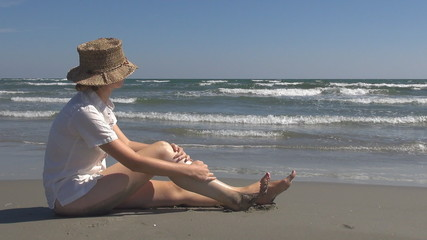 Woman applying sun protection on the beach