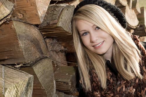 Hübsches blondes Mädchen lehnt sich an Holzstapel