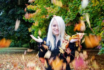schöne Frau mit fliegenden Herbstblättern