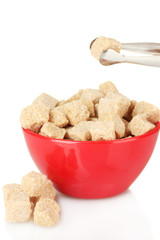 brown cane sugar cubes in bowl with sugar-tongs