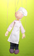 Wooden puppet as cook on green background