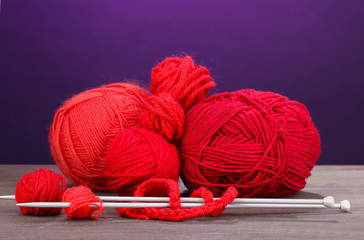 Red knittings yarns on wooden table on purple background