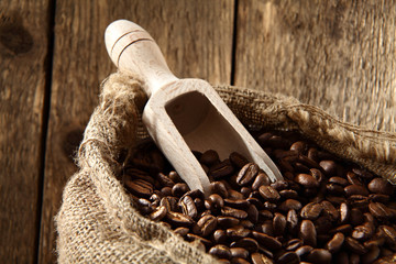 coffee beans in sack with wooden scoop