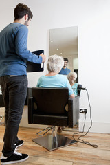 A hairdresser showing his client her new hairstyle in a mirror