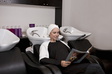 A female client reading a magazine in a hairdressing salon