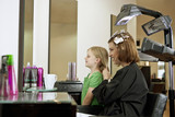 Mother and daughter looking in the mirror in a hairdressers
