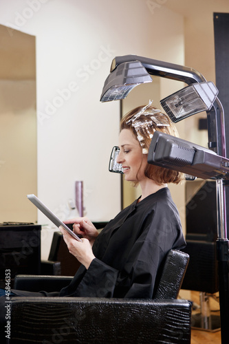 A woman using digital tablet whilst having her hair coloured
