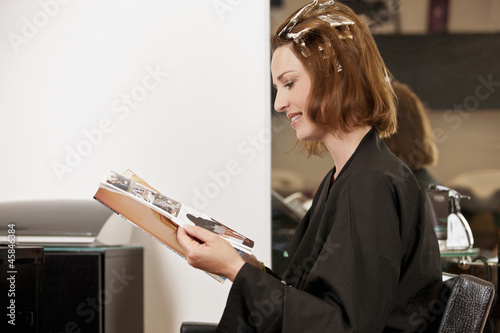 Woman reading a magazine whilst she has her hair coloured