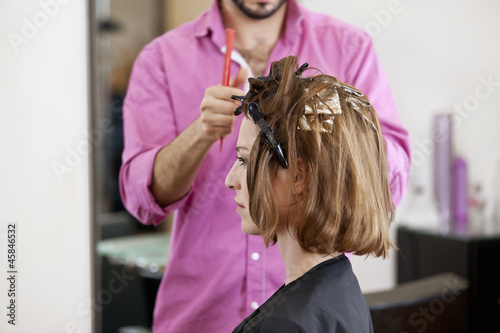 A hairdresser putting foils in a female clients hair