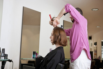 A male hairdresser preparing a female clients hair