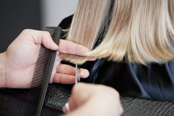 A male hairdresser cutting a young girls hair close up
