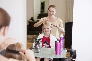A female hairdresser brushing a young girls hair
