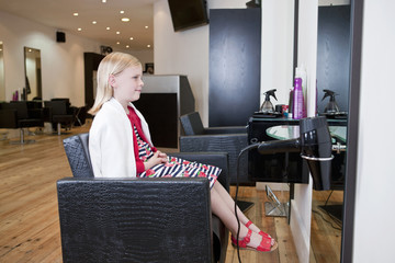 A young girl looking in a mirror at a hairdressing salon
