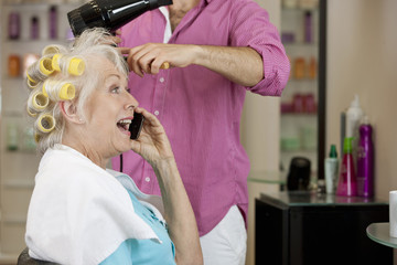 A senior woman on a mobile phone whilst having her hair dried