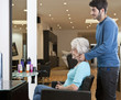 A senior woman in hairdressing salon admiring her new hairstyle