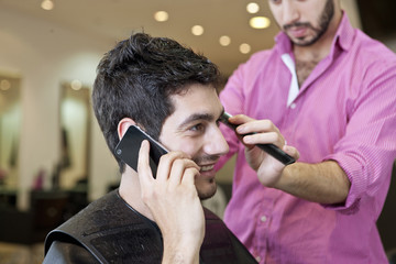 A male client on mobile whilst having his hair cut