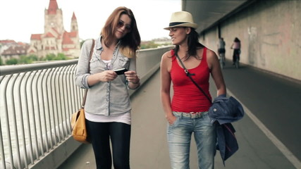 Female friends taking photo with cellphone in the city