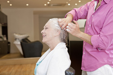 A male hairdresser applying product to womans hair, close up