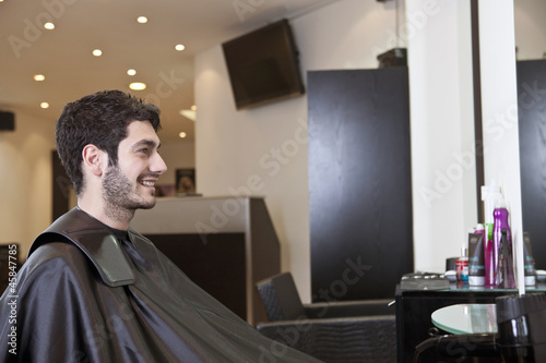 A male client looking in the mirror in a hairdressing salon