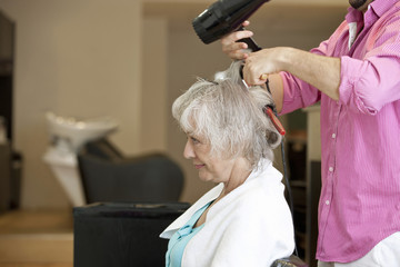 A senior woman having her blow dried at a hairdressing salon