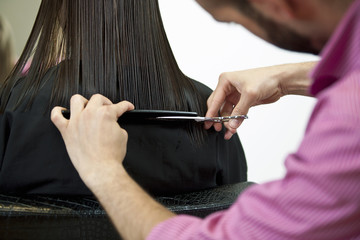A male hairdresser cutting womans long hair, close up
