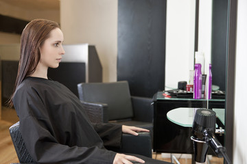A female client looking in a mirror at a hairdressing salon