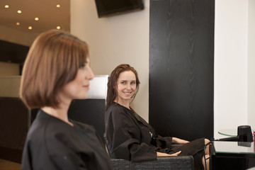 Two female clients sitting in a hairdressing salon