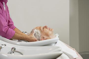 A senior woman having her hair shampooed at a hairdressing salon