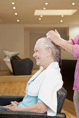Senior woman having product applied by hairdresser, close up